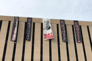 "Building with banners that read, ""tax cheat,"" ""wage thief"" and ""reject Puzder."""