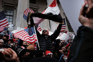 Brown man in black jacket holds red, white and black Yemeni flag above his head while surrounded by other Brown people holding red, white and blue American flags against grey building columns