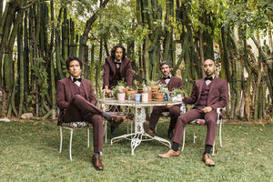 Four Brown men in matching maroon tuxedos near white table with green cacti on green grass near green trees and tall cacti