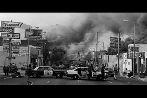 Black-and-white image of black-and-white police vehicles on a grey road near buildings and grey smoke