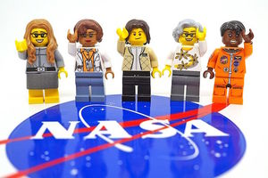 Two Black and three yellow Lego figures in multicolored outfits standing over red, white and blue logo against white background