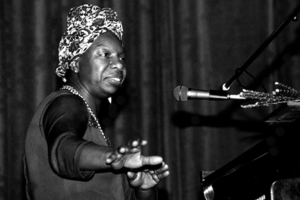 Black-and-white photo of Black woman in headwrap and black outfit seated at black piano with white keys near black microphone and stand