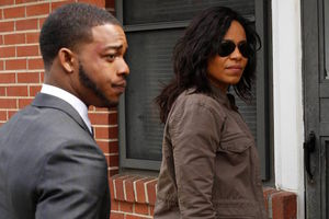 Black man in grey suit and white shirt next to Black woman in black sunglasses and brown-grey jacket in front of red brick wall and black window