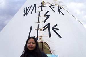 "Eva Cardenas stands before a tipi that reads, ""Water is life,"" at the National Mall on March 10, 2017."