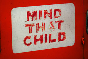 "Red and white sign reads ""Mind that child."""