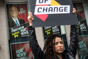 Black woman holds sign in front of poster of Bill O'Reilly