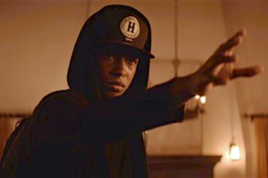 Black man in black hoodie and hat holding hand in front of brown wall