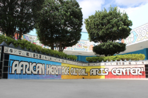 Black, blue, yellow, red and white mural on wall on grey cement in front of green trees and multicolored artwork and blue sky