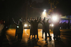 Black people in silhouette with hands raised stand in street under dim yellow light with blue and red police lights in the background