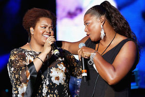 Black woman in brown blouse with white and yellow flowers embraces Black woman in black blouse in front of blurry blue background while holding black microphones