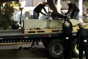 Statue on a flatbed truck with workers