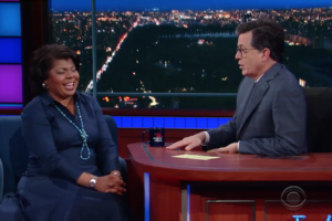 April Ryan and Stephen Colbert. Black woman in blue dress talks to White man in gray suit.