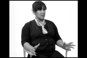 Greyscale image of Black woman in light patterned tie, black-and-white-striped vest and black shirt in front of white background
