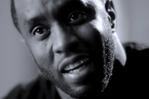 Black-and-white footage of Black man in front of blurry wall