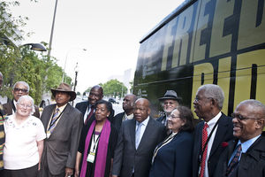 Group of Black and White women and men in multi-colored clothes in front of black bus with yellow text and green trees and grey sky