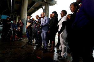 Black women and men in black, grey, blue and white clothing stand behind multicolored press microphones in front of grey sky and brown overpass