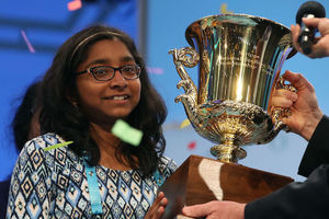 Brown girl in blue-and-brown-and-white shirt and black glasses holds gold trophy in front of blue background with multicolored confetti in air