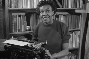 Black-and-white photo of Black woman in dark sweater and patterned skirt behind black typewriter with white paper in front of bookshelf,