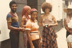 Black women and men in multi-colored clothing standing in front of brown buildings on brown sidewalk
