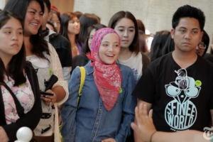 Brown girl in pink hijab and blue denim jacket stands surrounded by Asian boy and girls in black and white and pink clothing in front of grey wall