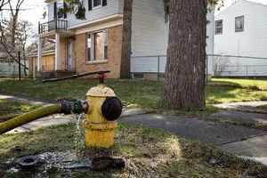 Yellow fire hydrant with yellow hose and blue top leaks brown water onto green grass in front of brown and white houses with black rails