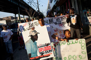Black woman in white shirt holds white sign with image of Black man while holding hand of Black boy with white sign in front of Black people in multicolored clothing holding white banner and walking on grey sidewalk