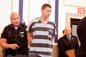 Ray Tensing. White man in black and white striped jail outfit, flanked by police officers.