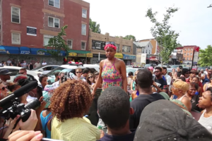 Black woman in pink, green and yellow dress surrounded by crowd with Black and White people in multicolored clothing on grey pavement near multicolored storefronts