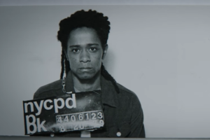 Black-and-white image of Black man holding black police sign with white text in imitation police line-up