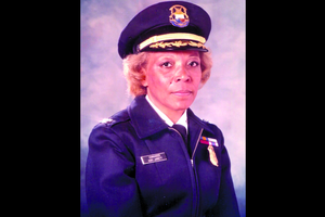 Black woman in navy cap and uniform with gold badge, black nametag with white text and multi-colored regalia in front of grey background