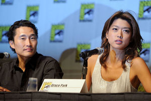 Asian man in black shirt sits next to Asian woman in grey tank top behind Black table and white wall with black and yellow images and text