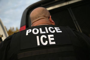 """Man with """" POLICE ICE"""" emblazoned on his back in white letters"""