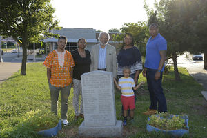 Black men, women and child in multicolored clothing stand behind gray gravestone on green cemetery grass in front of green-and-brown trees and grey building