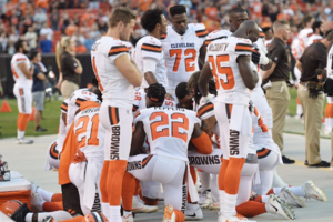 Black men in white and orange and brown and black jerseys kneel in circle on green grass