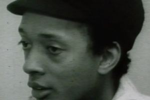 Black-and-white image of Black man in black hat and white shirt in front of grey background