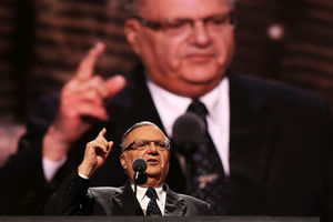Joe Arpaio stands at a podium and gestures with his index finger. An image of himself is blown up on a screen behind him.