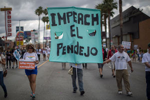 "Protestors carry sign that reads ""Impeach el pendejo."""
