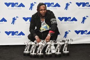 Black man in black outfit kneels behind six silver statues on black floor in front of white screen with blue images and text