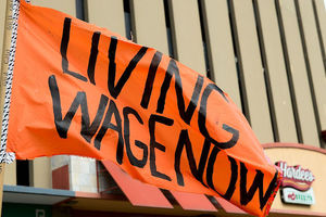 "Orange flag says, ""Living wage now."""