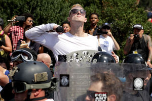 "A White man in sunglasses and a White shirt makes a slashing motion across his neck during the ""Unite the Right"" rally in Charlottesville, Virginia"