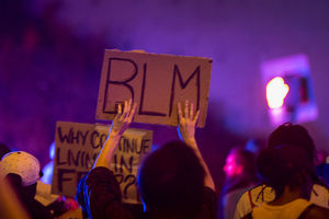 "Protester holds sign that says ""BLM."""