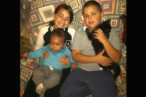 Black girl in black-and-white jumpsuit holds Black baby boy in blue shirt and grey pants while sitting next to Black boy in grey shirt and navy pants holding black cat with white paws while seated on multicolored couch