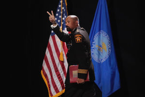 Black man in black police uniform with yellow insignia holds red folder in front of red, white and blue U.S. flag and black background