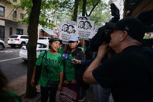 "Two women in green t-shirts talk to a reporter as people behind them hold black and white signs that say ""Justice for Edith and Shirley."""