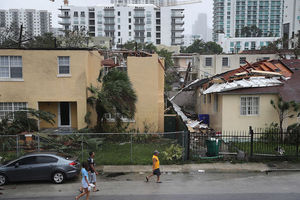 People walk past the building where the roof was blown off by Hurricane Irma on September 10, 2017 in Miami, Florida.