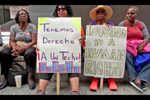 """Two protestors hold up signs. One of them says in Spanish, """"We Have Right to A Roof."""" The other one says, """"Housing is a human right!"""""""