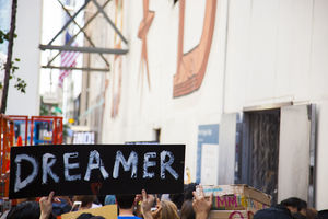 "A black sign with white writing that says ""Dreamer"""