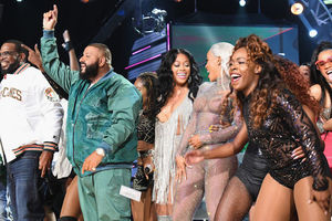 Black man in white jacket and blue jeans next to Brown man in teal tracksuit next to Black woman in silver dress next to Black woman in silver body suit next to Black woman in black body suit, all in front of Black men and women in multicolored clothing