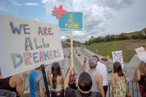 """Protesters, some hold sign that reads, """"We are all dreamers."""""""