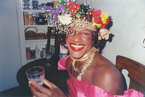 A Black woman with an assortment of flowers in her hair holding a glass and smiling.